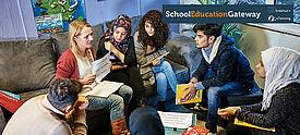 Fünf junge Menschen sitzen im Kreis mit einer Deutschlehrerin