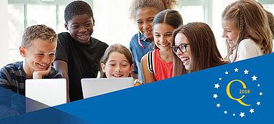 Sieben Schülerinnen und Schüler fröhlich vor zwei Laptops