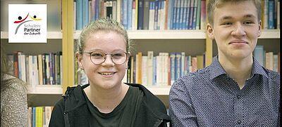 Eine Schülerin und ein Schüler sitzen vor einer Bücherwand