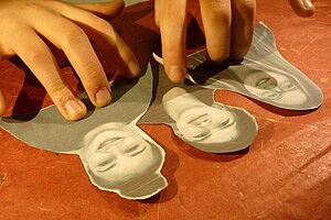 Papierfiguren werden auf Tisch gelegt
