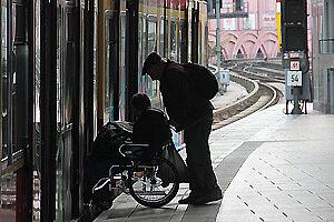 Mann in Rollstuhl besteigt einen Zug