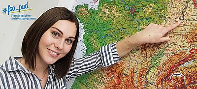 Junge Frau zeigt auf Frankreich-Karte