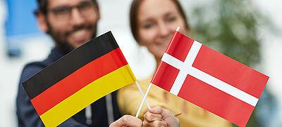 Junger Mann und junge Frau halten deutsche und dänische Fahne in die Kamera