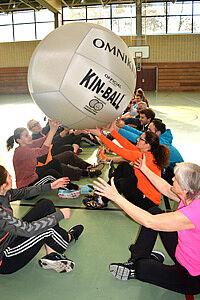 Erwachsene mit Riesenball sitzen auf dem Boden einer Turnhalle