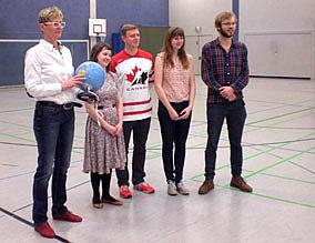 Fünf Personen stehen in einer Turnhalle