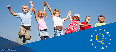 sechs Kinder auf einer Wiese springen hoch