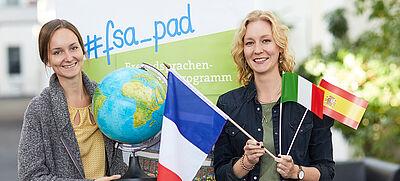 Zwei junge Frauen mit Flaggen und Globus vor FSA-Logo