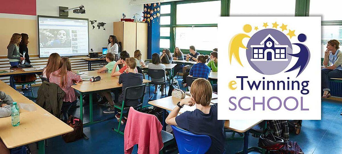Klassenraum mit Schüler/-innen und dem Logo des eTwinning-Schulsiegels