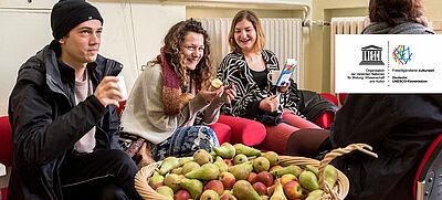 4 junge Menschen mit einem Korb voller Äpfel und Birnen