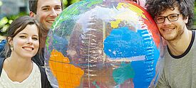 Drei Erwachsene mit einer Weltkugel als Wasserball