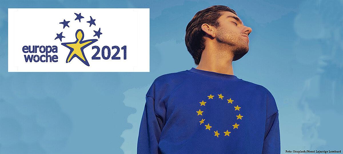 Lehrer mit EU-Pullover vor blauem Hintergrund, links davon das Logo der Europawoche 2021