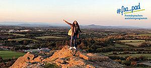 Junge Frau steht auf einem Berg