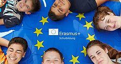 6 Kinder liegen auf einer Europafahne