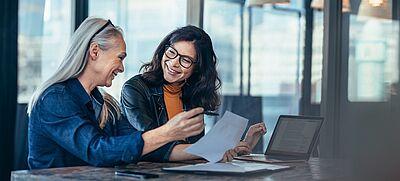 Zwei Frauen mit Laptop unterhalten sich