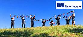 Schüler auf grünem Hügel halten europäische Fahnenkette, daneben ist Erasmus+ Logo