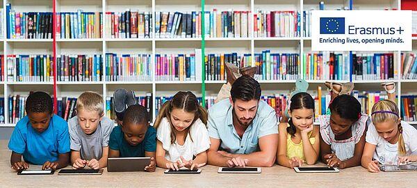 Lehrer liegt mit Grundschülern auf dem Boden einer Bibliothek, alle schauen in Tablets