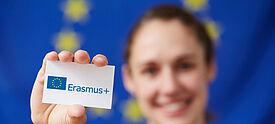 """Frau hält """"Erasmus+ Schulbildung"""" Kärtchen in die Kamera"""