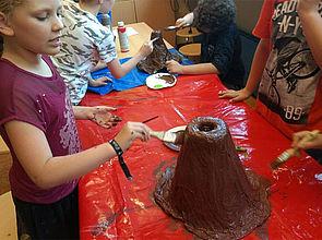 Schüler streichen einen Berg aus Pappmache braun an