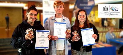 Drei junge Erwachsene mit Urkunden