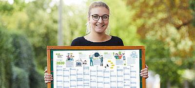 Frau hält Kalender in die Höhe