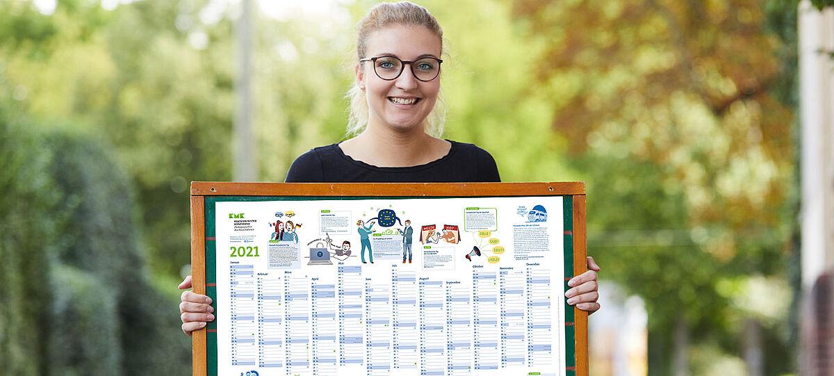 Junge Frau hält Plakat mit Kalender vor sich
