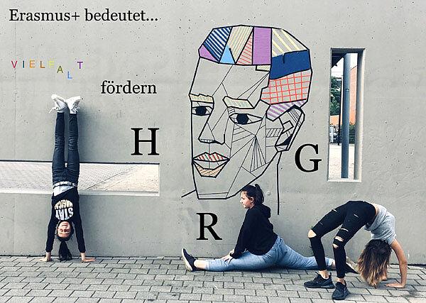 3 Mädchen machen Turnübungen vor Schulwand mit Zeichnung