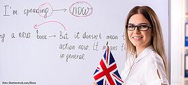 Lehrerin mit britischer Flagge im Klassenzimmer beim Englischunterricht