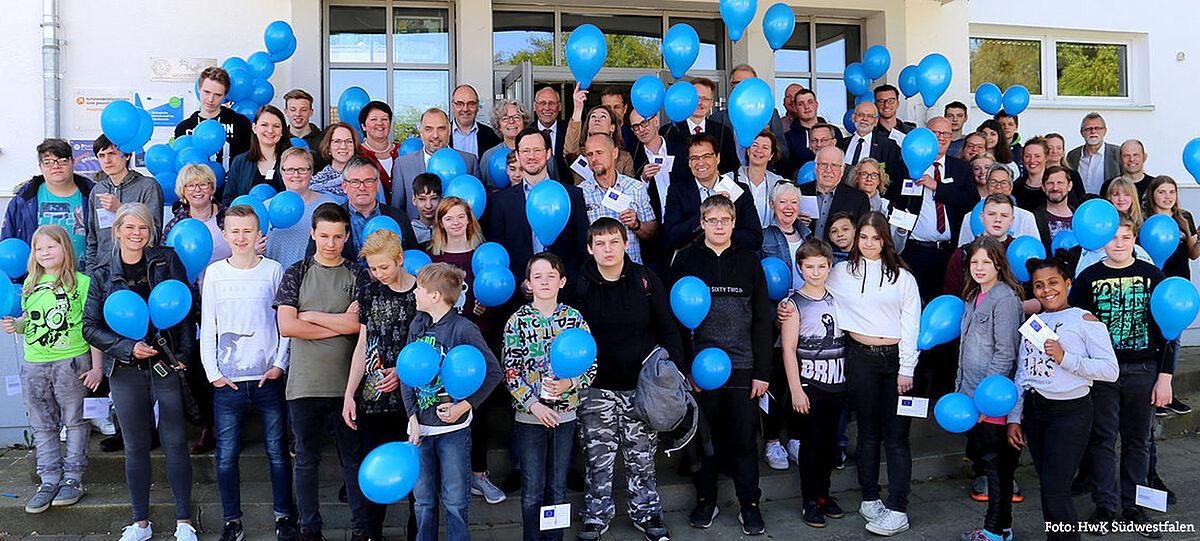 Gruppe von Kindern und Erwachsenen mit blauen Luftballons