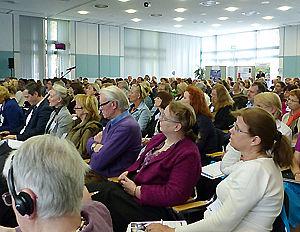 Viele Erwachsene sitzen bei einer PAD-Veranstaltung in einem Saal und hören zu