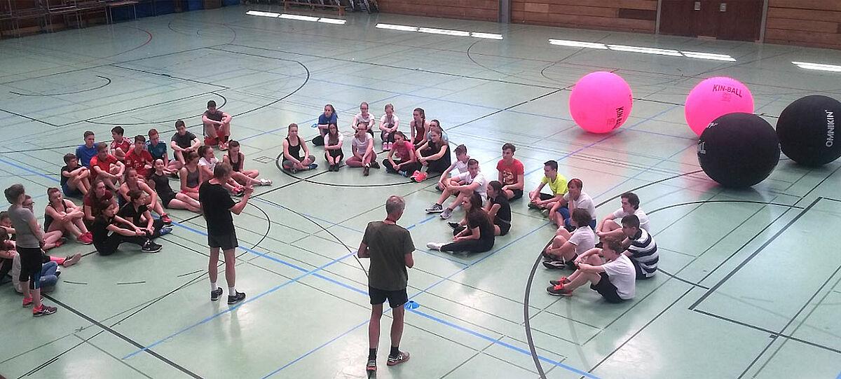 Schüler sitzen auf dem Boden in Turnhalle. Im Hintergrund große Bälle.