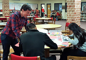 Schüler in der Bibliothek arbeiten an einem Tisch