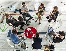Sieben junge Menschen sitzen in einem Stuhlkreis, der auf dem Boden eines stillgelegten Schwimmbads aufgebaut ist.