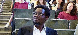 Der ehemalige Preisträger John Tumusiime im einem Hörsaaal, im Hintergrund Teilnehmerinnen und Teilnehmer aus dem Internationalen Preisträgerprogramm