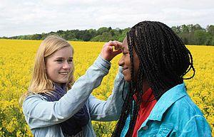 Zwei Schülerinnen vor einem blühenden Rapsfeld
