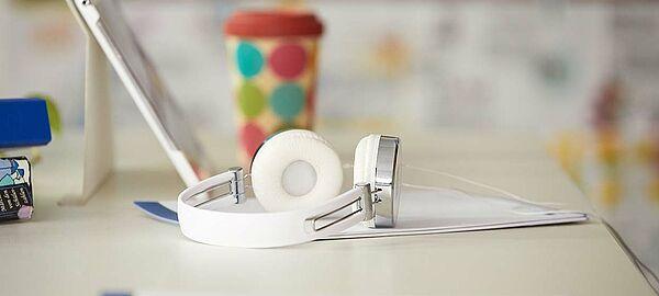 Kopfhörer, Notebook und Schreibmaterial auf Tisch