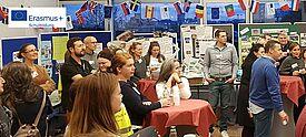 Gruppe von Lehrerinnen und Lehrern stehen in einem mit Fahnenkette geschmückten Raum