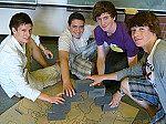 Schülergruppe mit Steinen
