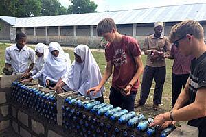 Jugendliche bauen an einer Mauer aus Flaschen