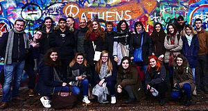 Menschen vor einer Mauer mit Aufschriften