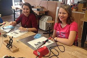 Zwei Schülerinnen mit Lötkolben an Arbeitstisch