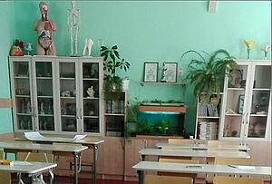 Blick ins Klassenzimmer mit Regalen und mintgrüner Wand