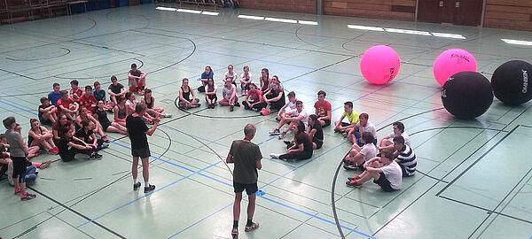 Schüler sitzen in Turnhalle auf dem Boden mit großen Bällen im Hintergrund