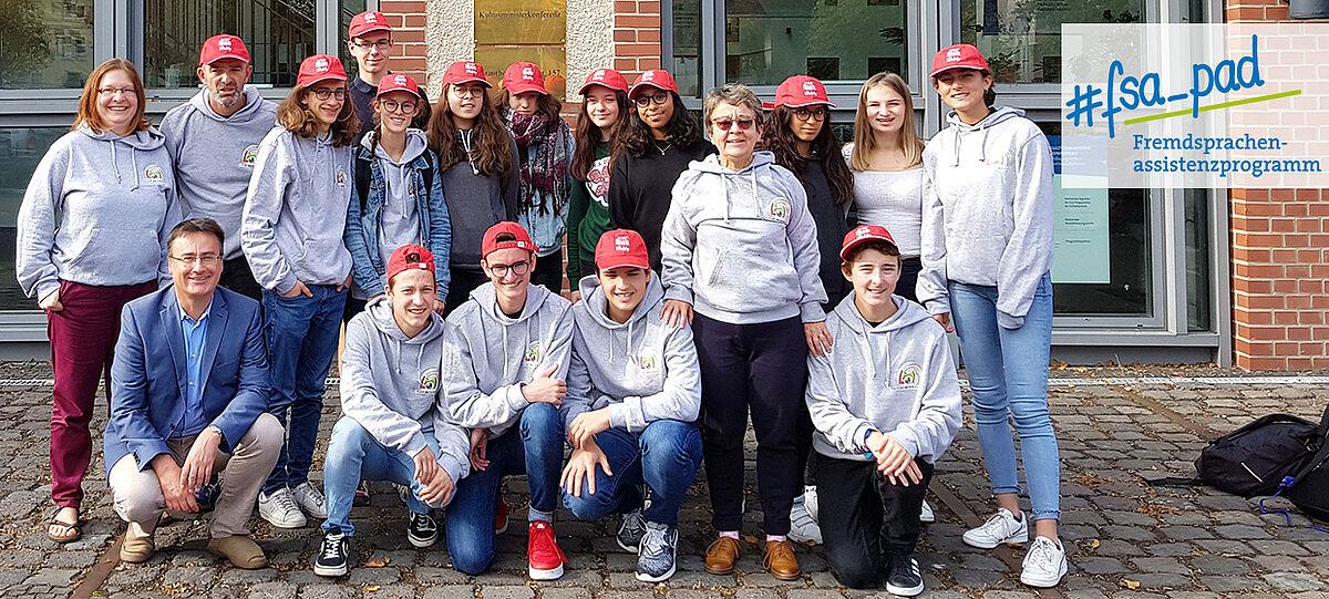 Schülergruppe mit vier Erwachsenen vor Gebäude