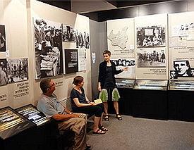Eine Frau erläutert zwei weiteren Personen Infotafeln zum Holocaust.