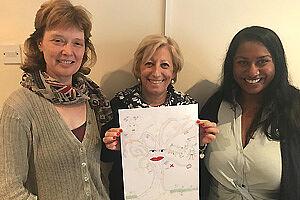 Drei Frauen stehen nebeneinander und halten die Zeichnung eines Baumes hoch