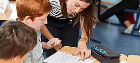 Junge Lehrerin erklärt Schülern etwas