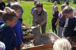 Schüler und Lehrerin bei Gartenarbeit