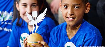 Schülerin und Schüler halten Auszeichnung des Deutschen Schulpreises in der Hand