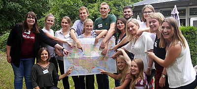 Gruppe junger Frauen und Männer mit USA-Karte
