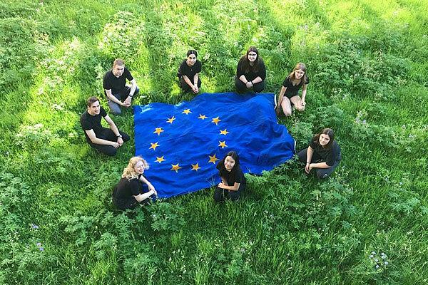 Schüler*innen mit Europafahne im grünen Gras von oben fotografiert